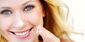 Pige smører fugtighedscreme i ansigtet